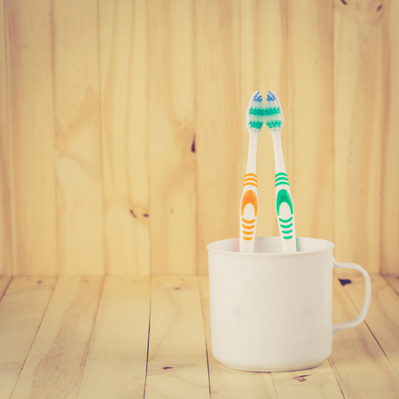 Toothbrushes in cup on wooden table with retro filter effect Stock Photo