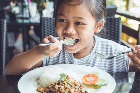 ni�a comiendo: Cierre de ni�os tailandeses que comen en restaurante Foto de archivo