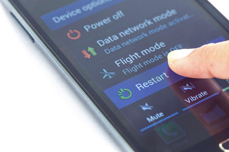 restart: Close up finger press Restart button on smartphone Stock Photo