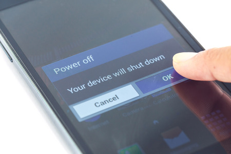 Close up finger press power off button on smartphone