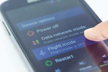flight mode: Close up finger press flight mode button on smartphone Stock Photo