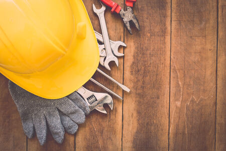 zapatos de seguridad: Close up de una variedad de herramientas de trabajo sobre fondo de madera