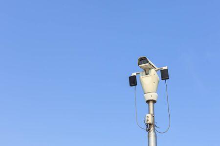 CCTV security camera on blue sky background photo