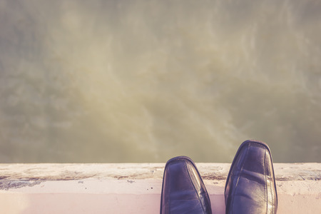 Feet with black shoe Standing on Cement Edge, suicide concept