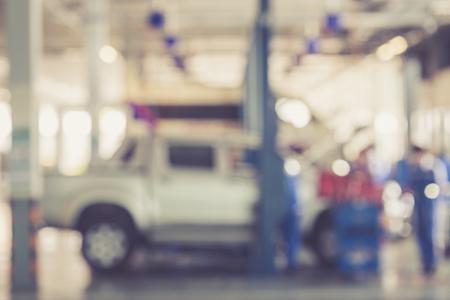 Blurred background : Thai people repairing the car in garage vintage color