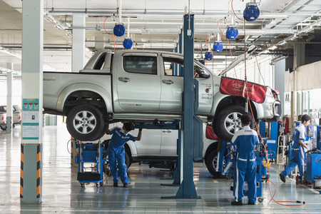 scheduled replacement: PHUKET, THAILAND - MARCH 10 : Car technician repairing car in workshop service station in Phuket on March 10, 2015. The official dealer of Toyota, who is the top market share for commercial car.