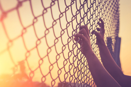 Hand holding on chain link fence, Vintage filter effect