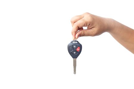 llaves: Llave del coche sosteniendo a mano aislado sobre fondo blanco