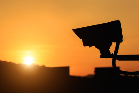 city surveillance: Close up silhouette of Security CCTV camera with sunset background Stock Photo