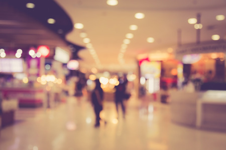 store display: Blurred image of people in shopping mall with bokeh, vintage color Stock Photo