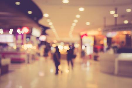 Image floue de personnes dans un centre commercial avec bokeh, la couleur millésime