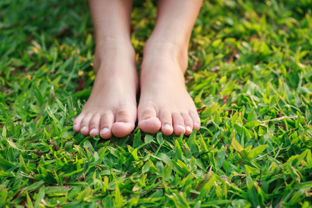 grass flower: Close up children feet on green grass in the park Stock Photo
