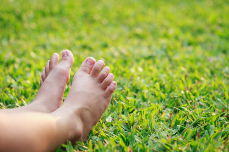 Close up children feet on green grass in the park Stock Photo