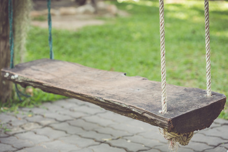 Close up old wooden swing in the garden photo