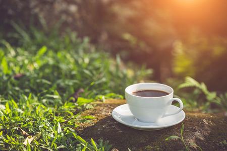 Bouchent la tasse de café blanc dans le jardin au matin