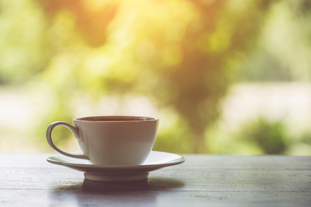 breakfast garden: Close up white coffee cup on the table at morning time Stock Photo