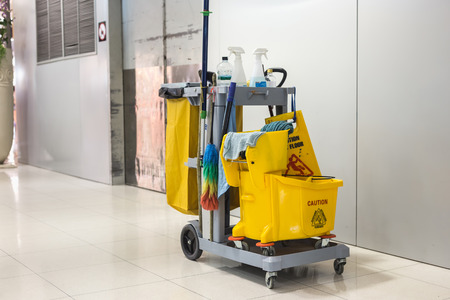 janitorial: Yellow mop bucket and set of cleaning equipment in the airport