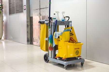 Yellow Putzeimer und Satz von Reinigungsgeräten in Flughafen