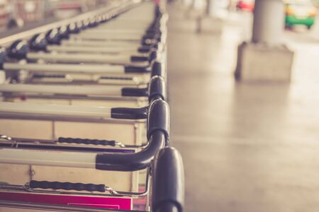 Close up trolleys luggage in a row in airport, retro filter effect photo