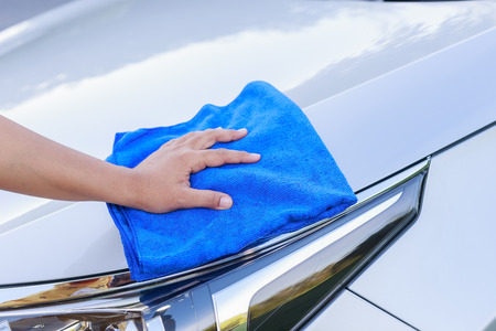 Close up woman hand with blue microfiber cloth cleaning the car