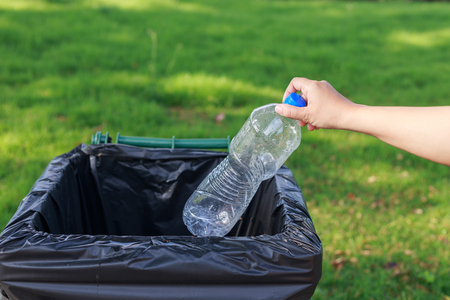 segregate: Close up hand throwing empty plastic bottle into the trash Stock Photo