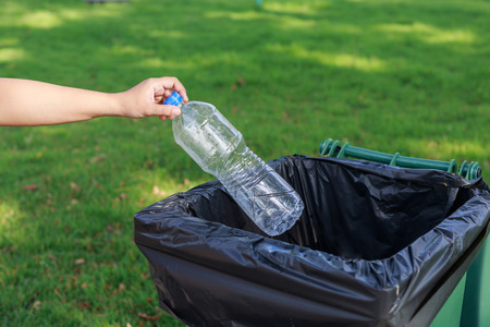 Close up hand throwing empty plastic bottle into the trash Stock Photo