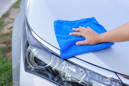 autolavaggio: Chiuda sulla mano di donna con un panno in microfibra blu pulitura dell'automobile
