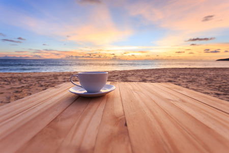 夕日や日の出のビーチで木製テーブルの上のコーヒー カップを閉じる