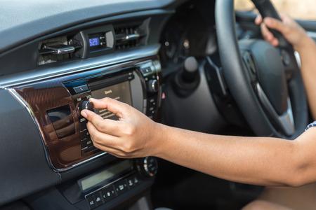 Close-up bestuurder kant audio-knop aan te passen in de auto