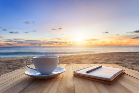 morning coffee: Close up coffee cup on wood table at sunset or sunrise beach