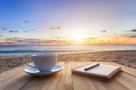 Close up Kaffee-Tasse auf Holztisch bei Sonnenaufgang oder Sonnenuntergang am Strand