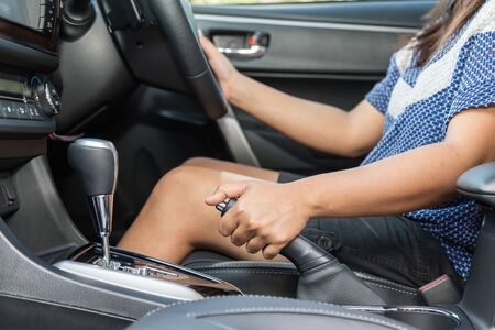 hand brake: Close up driver pulling the hand brake in car
