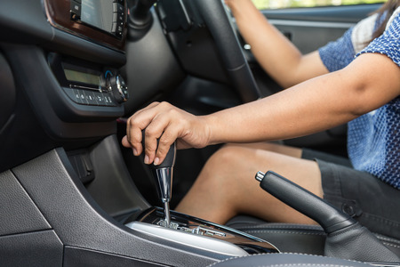 Close up driver left hand shifting the gear stick in car photo