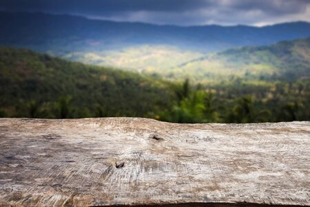 backdrop: Close up old wood table top with blur mountain background