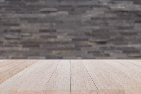 Close up empty top wood table and stone wall background. For product display