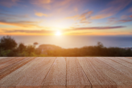 Close up top wooden table and blur sunset background