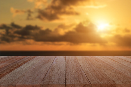 view to outside: Close up top wooden table and blur sunset background