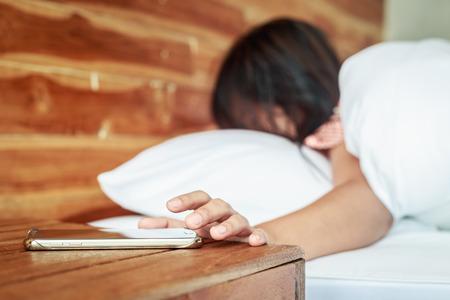 Close up smartphone toucher de la main sur la table et de la femme en bois sur le lit