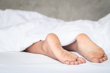 white pillow: Close up feet of women on white bedding in the morning time Stock Photo