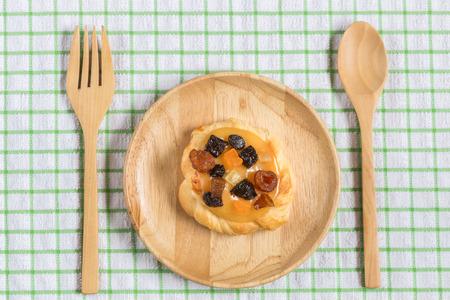 frutas secas: Close up natillas danés con fruta seca mezclada en plato de madera
