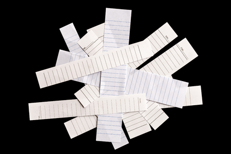 looseleaf: Close up piece of white lined paper isolated on black background