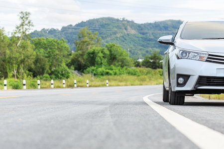 New silver car parking on the asphalt road in Thailand