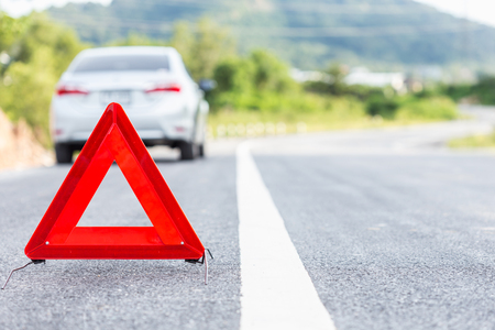 roadside assistance: Red emergency stop sign and broken silver car on the road Stock Photo