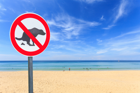 pooping: Round no dog pooping sign on the beach Stock Photo