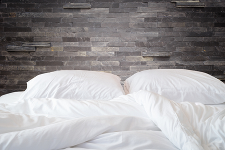 bedding: Close up white bedding sheets and pillow on natural stone wall room background, Messy bed concept Stock Photo