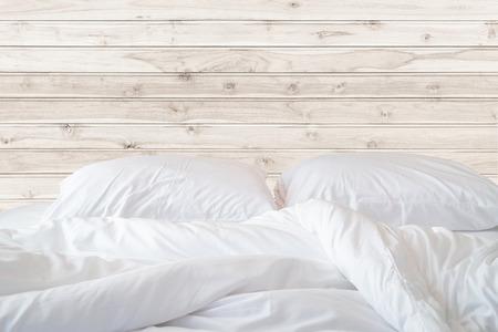 Close-up wit beddengoed lakens en kussens op houten muur kamer achtergrond, Messy bed-concept Stockfoto