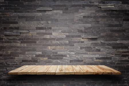 trompo de madera: Vacíos estantes superiores de madera y fondo de la pared de piedra. Para la exhibición del producto Foto de archivo