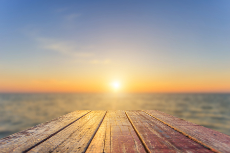 Close up top of old wooden table with blur sunset  background Stockfoto