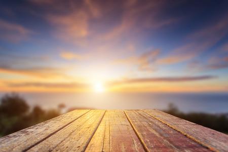 Close up oben auf der alten Holztisch mit Unschärfe Sonnenuntergang Hintergrund