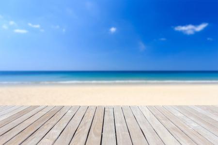 나무 갑판 또는 바닥과 열대 해변을 닫습니다